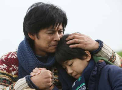 険しい顔をする織田裕二と下を向く子供